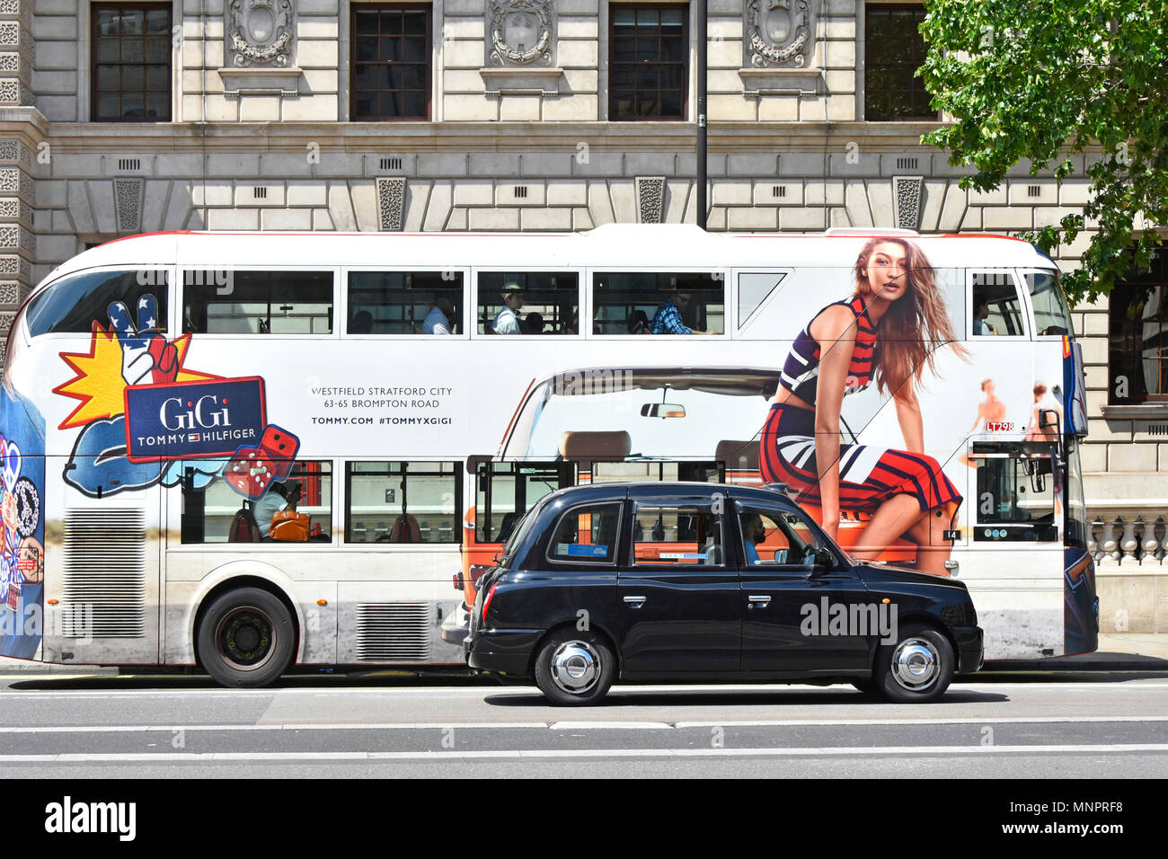 Whitehall London street scene black cab passing advertisement side view of London public transport bus with fashion model sitting on front of taxi UK Stock Photo