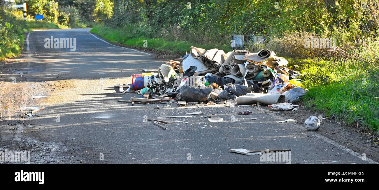 Fly tipping of lorry load of assorted waste rubbish garbage dumped on a public highway in a country lane Brentwood Essex countryside England UK - Stock Image