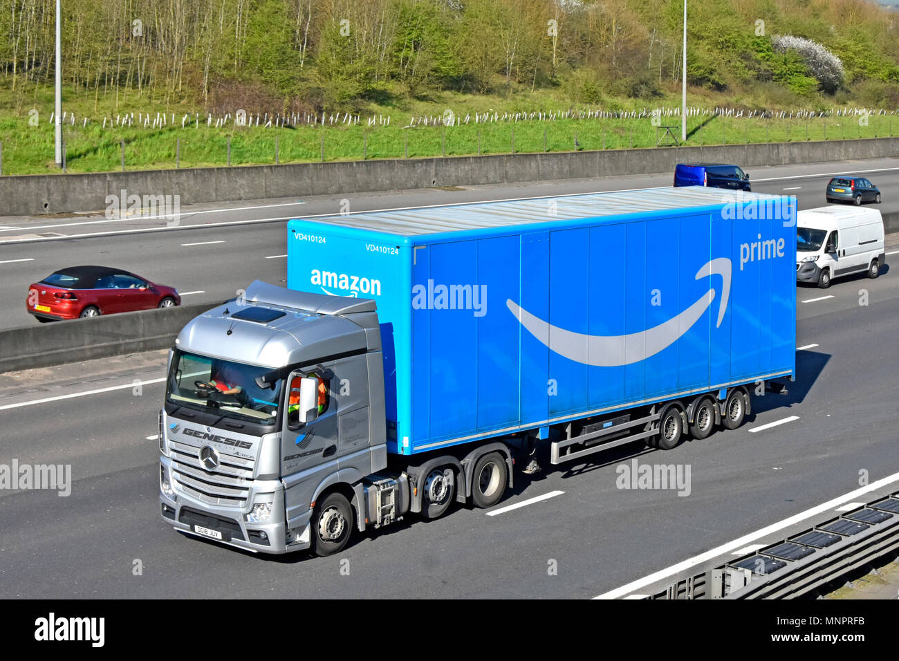 Front & side of Mercedes hgv transport logistics lorry truck & blue articulated trailer advertising Amazon brand Prime service & logo on UK motorway - Stock Image