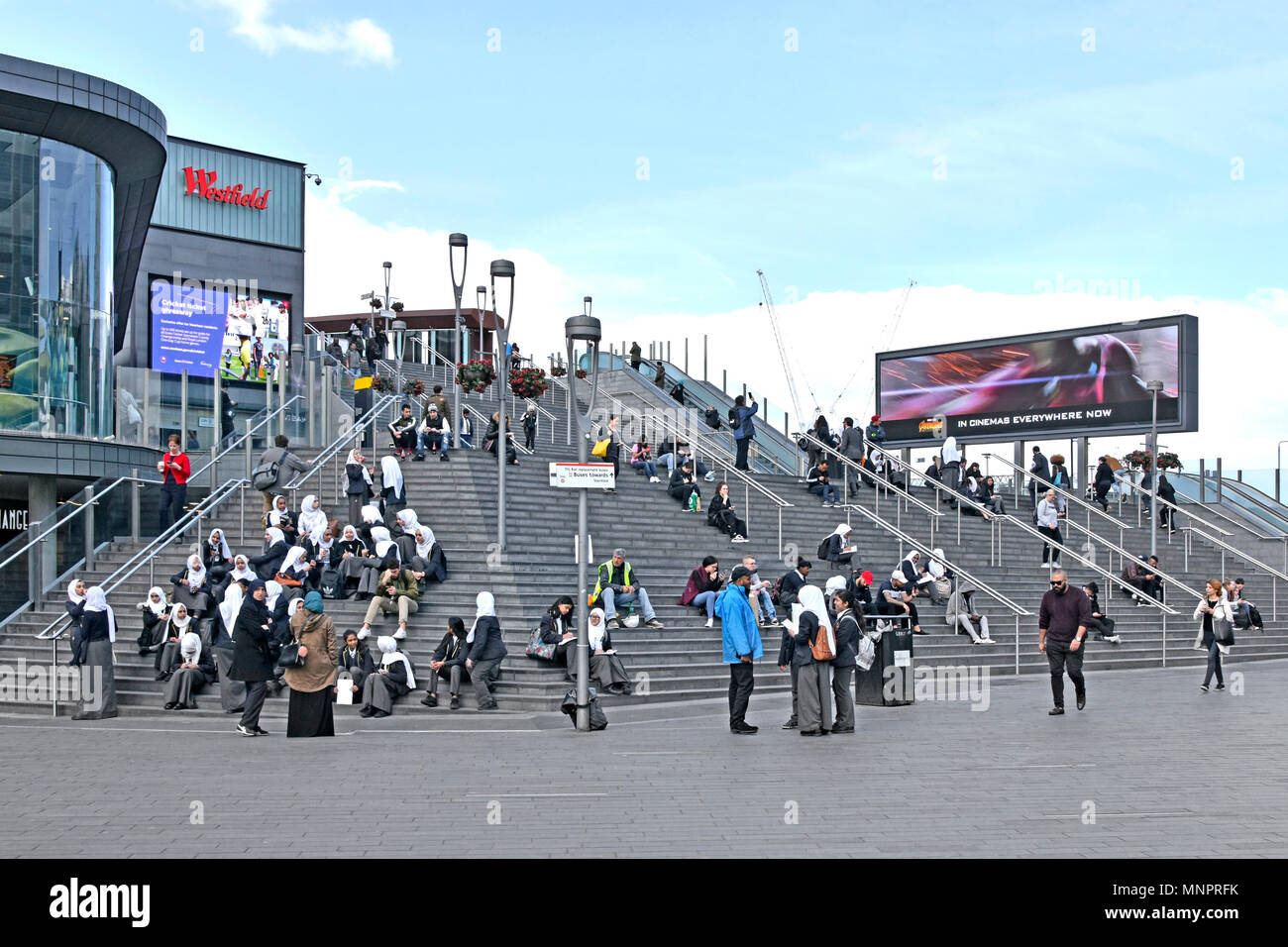 Girl school children in uniform many wearing hijab with staff on steps up to Westfield shopping centre multicultural Stratford Newham East London UK - Stock Image