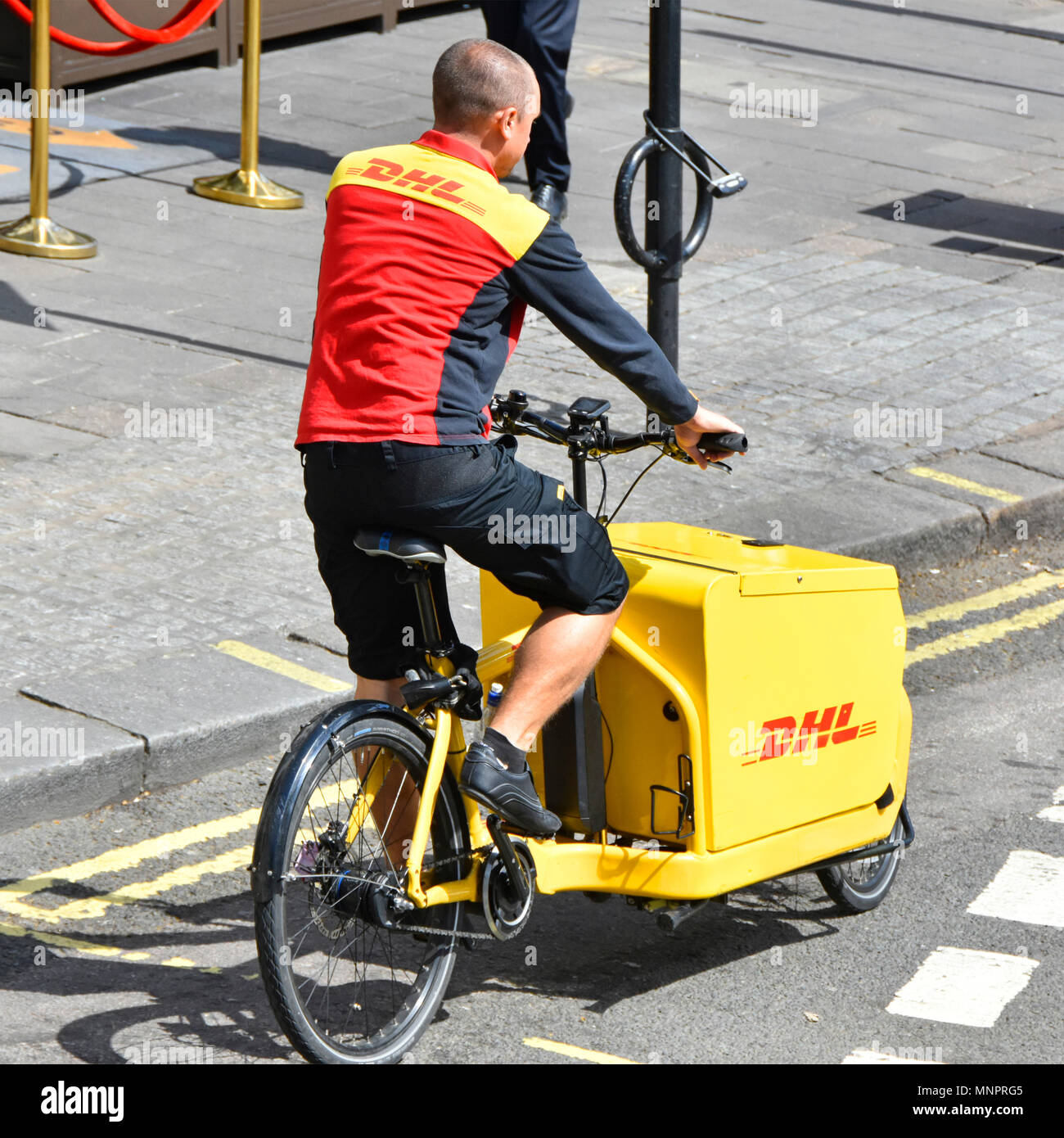 Unusual employment job DHL parcel delivery man in uniform working at