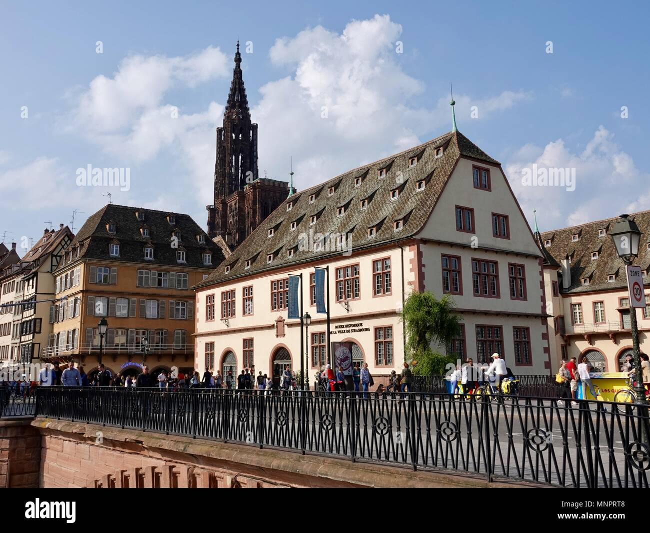 People walking in front of the Musee Historique de la Ville de Strasbourg with cathedral in background, Strasbourg, France - Stock Image