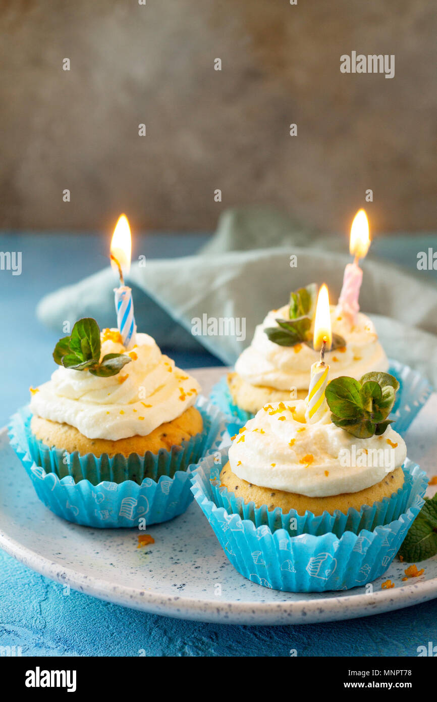 Colorful orange cupcake with birthday candle on a blue a stone or slate background. - Stock Image