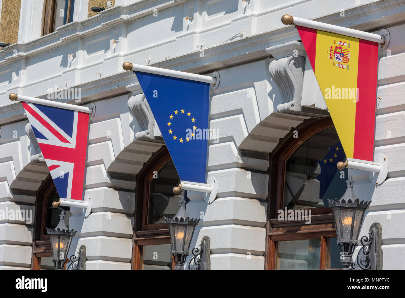 Spanish, british and European flags all flying together outside of a large classically designed building with arches. flagpoles and European emblems. - Stock Image