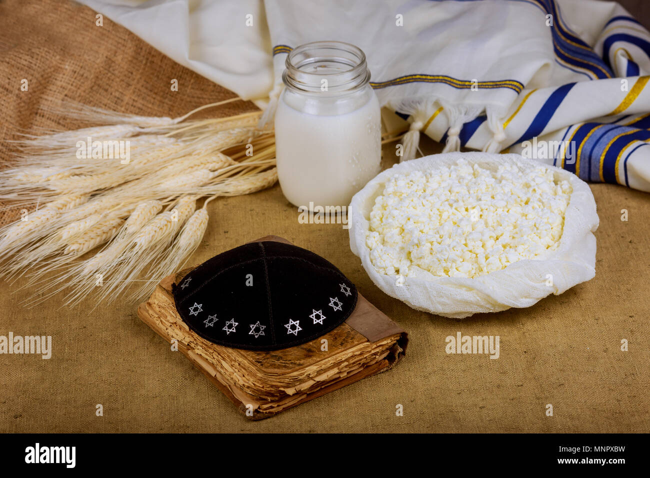 Dairy products on wheat field table torah, Symbols of jewish holiday - Shavuot - Stock Image