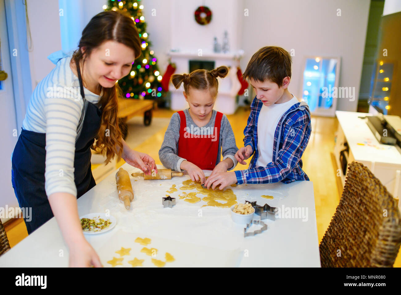 Family of mother and kids baking cookies at home on Xmas eve. Beautifully decorated room, Christmas tree and lights on background. - Stock Image