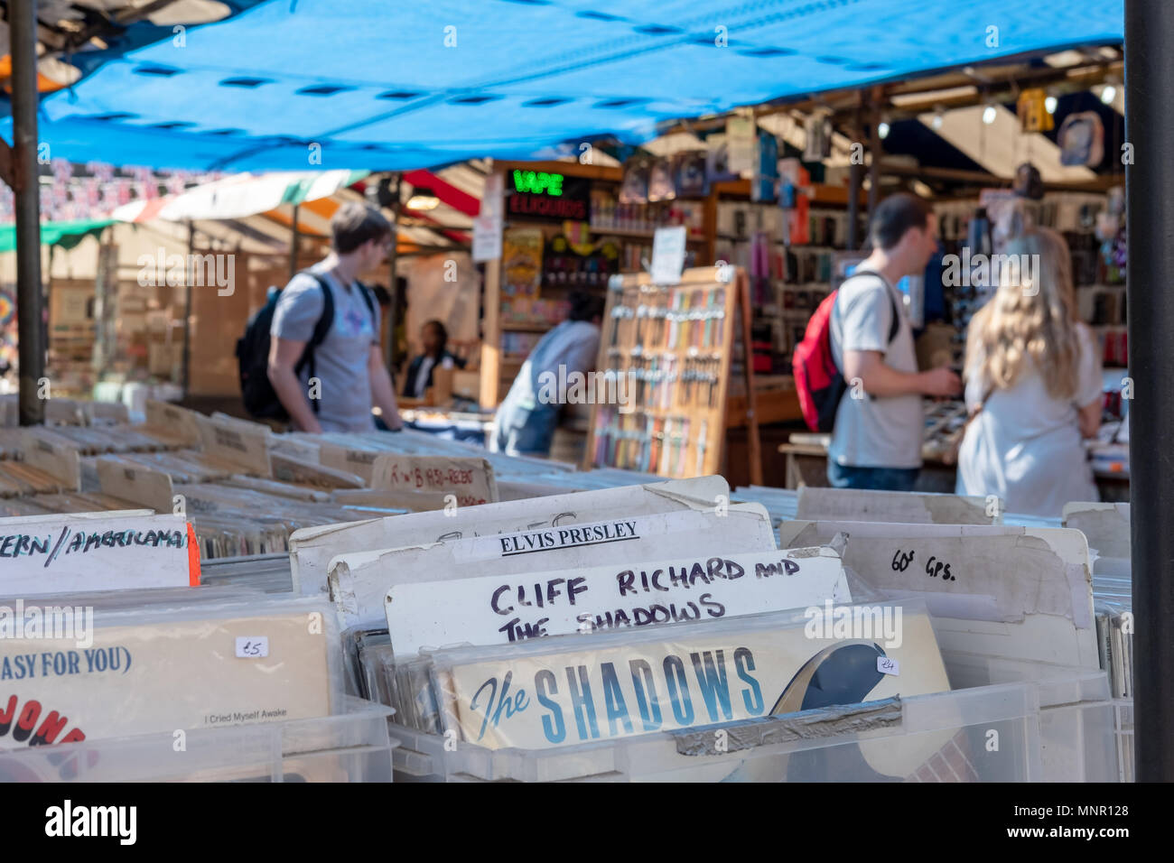 Shallow focus view of nostalgic, vinyl records being sold in an English flea market. The background shows members of the public visiting the stalls. - Stock Image