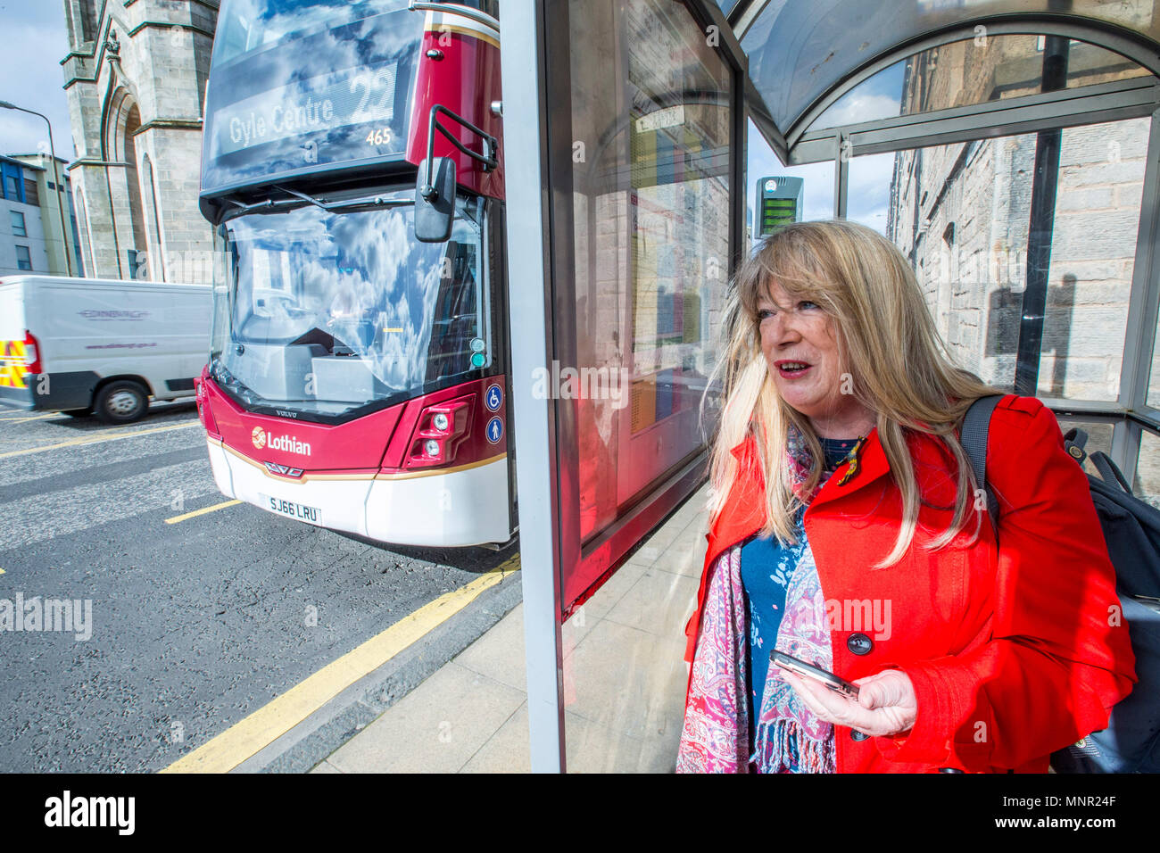 Woman waiting on bus at bus stop Stock Photo