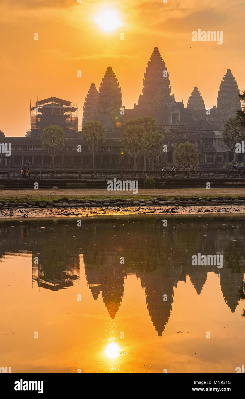 Sunset in Angkor Wat temple complex, Siem Reap, in Cambodia. The temple is reflected in the water - Stock Image