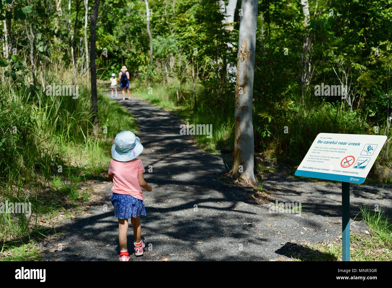 A mother and children walk along a path in a forest, Jourama Falls, Bruce Hwy, Yuruga QLD, Australia - Stock Image