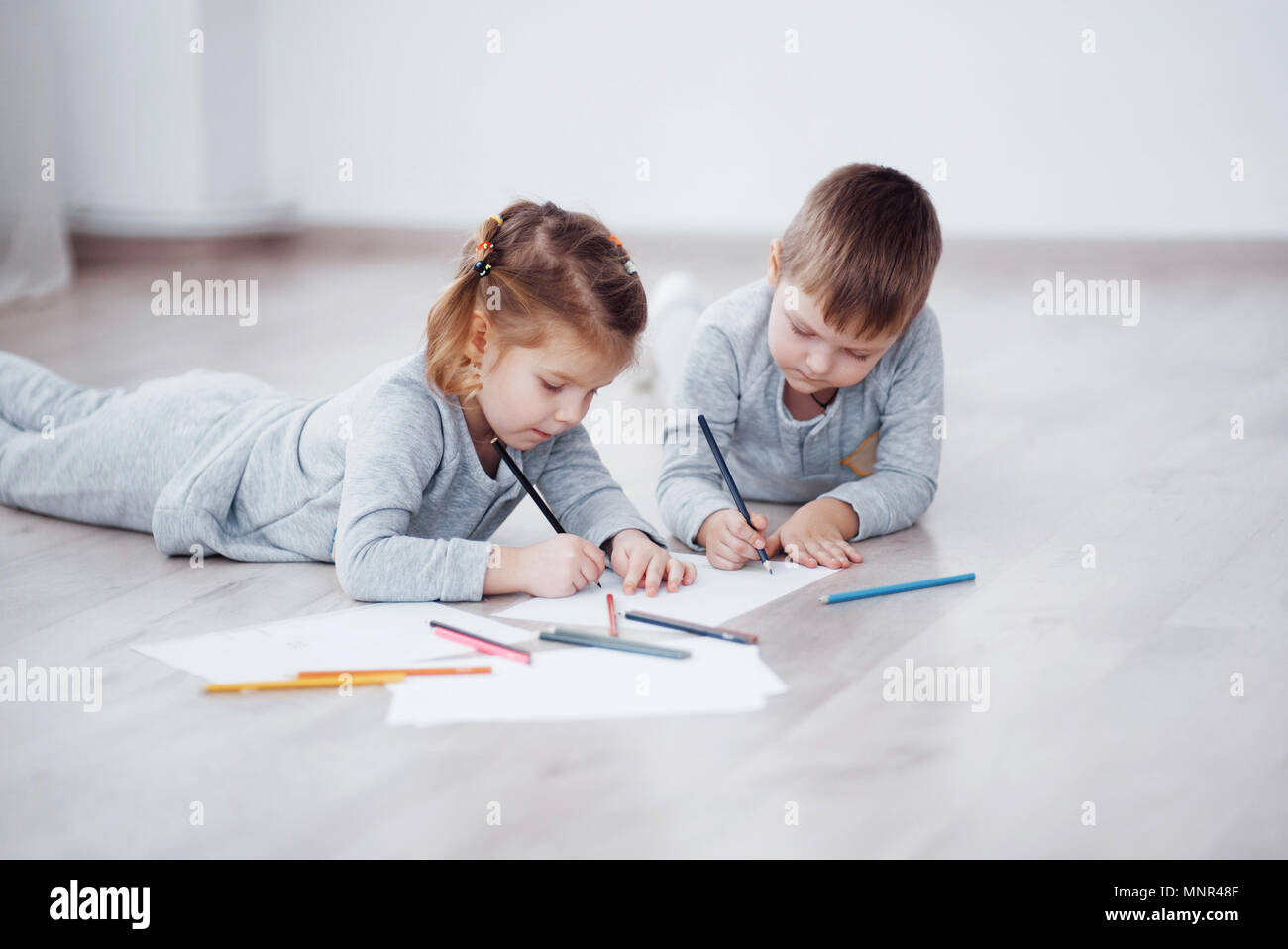 Children Lie On The Floor In Pajamas And Draw With Pencils Cute