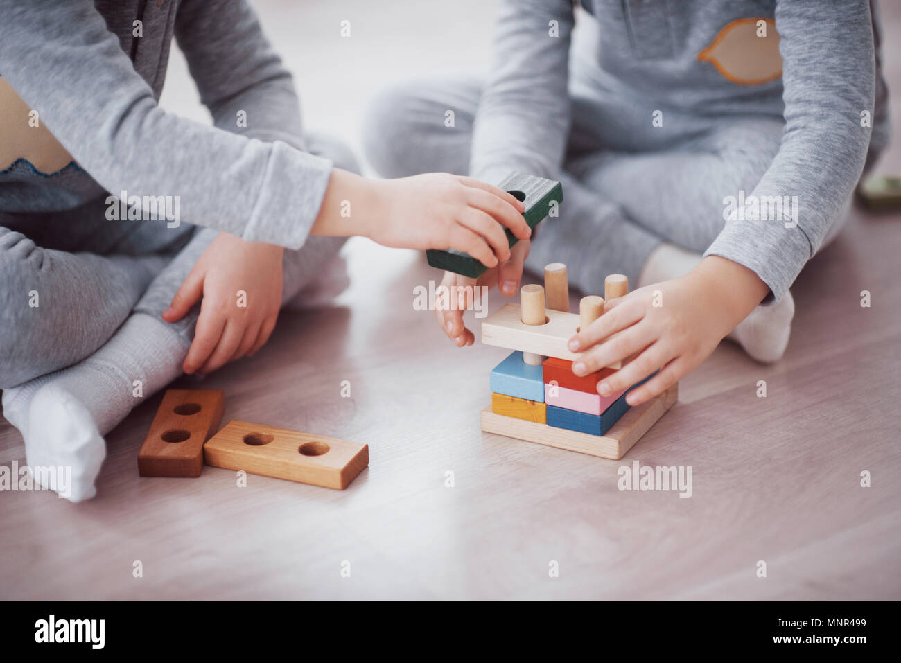 Children play with a toy designer on the floor of the children's room. Two kids playing with colorful blocks. Kindergarten educational games - Stock Image
