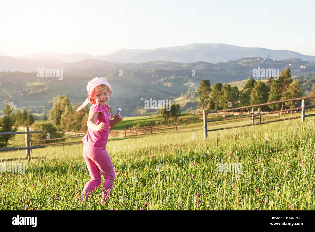 Cute happy little baby girl play outdoors in the early morning in the lawn and admiring mountains view. Copy space for your text - Stock Image