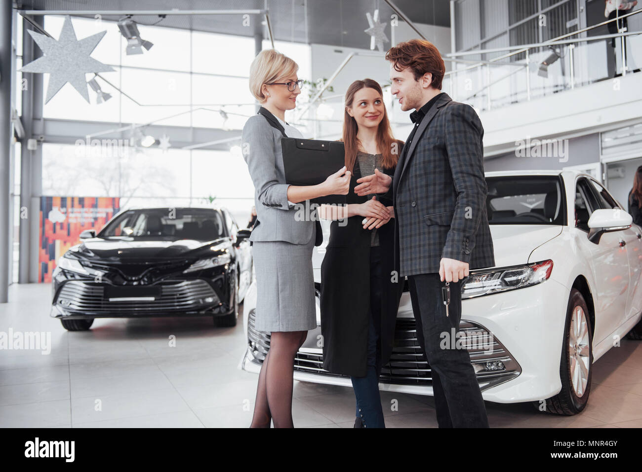 Proud owners. Beautiful young happy couple hugging standing near their newly bought car smiling joyfully showing car keys to the camera copyspace family love relationship lifestyle buying consumerism - Stock Image