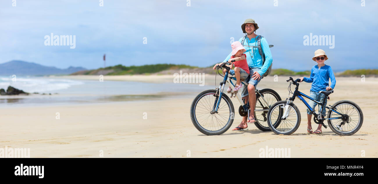 Father and kids riding bikes along a beach - Stock Image