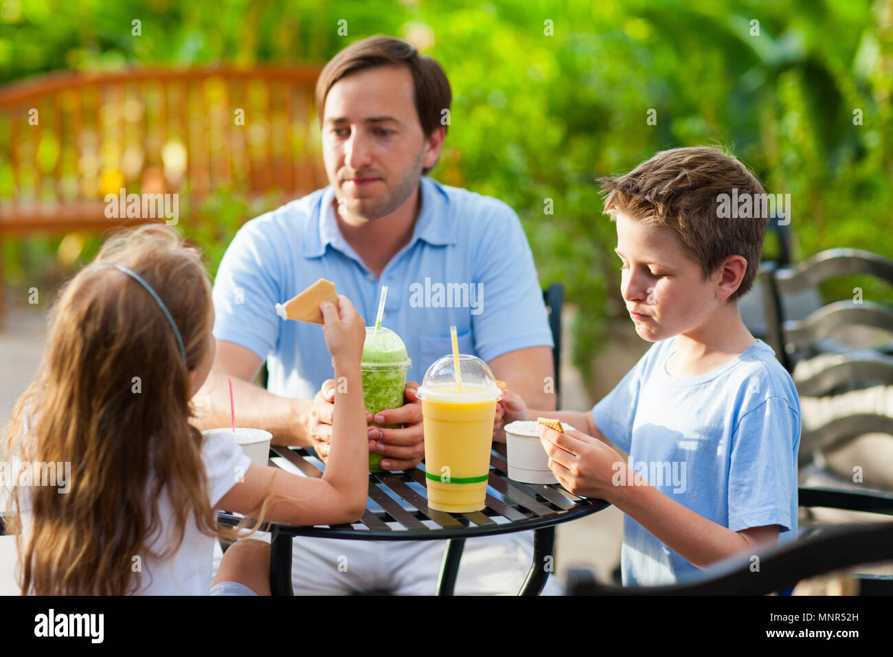Young father and his two kids at outdoor cafe on summer day - Stock Image