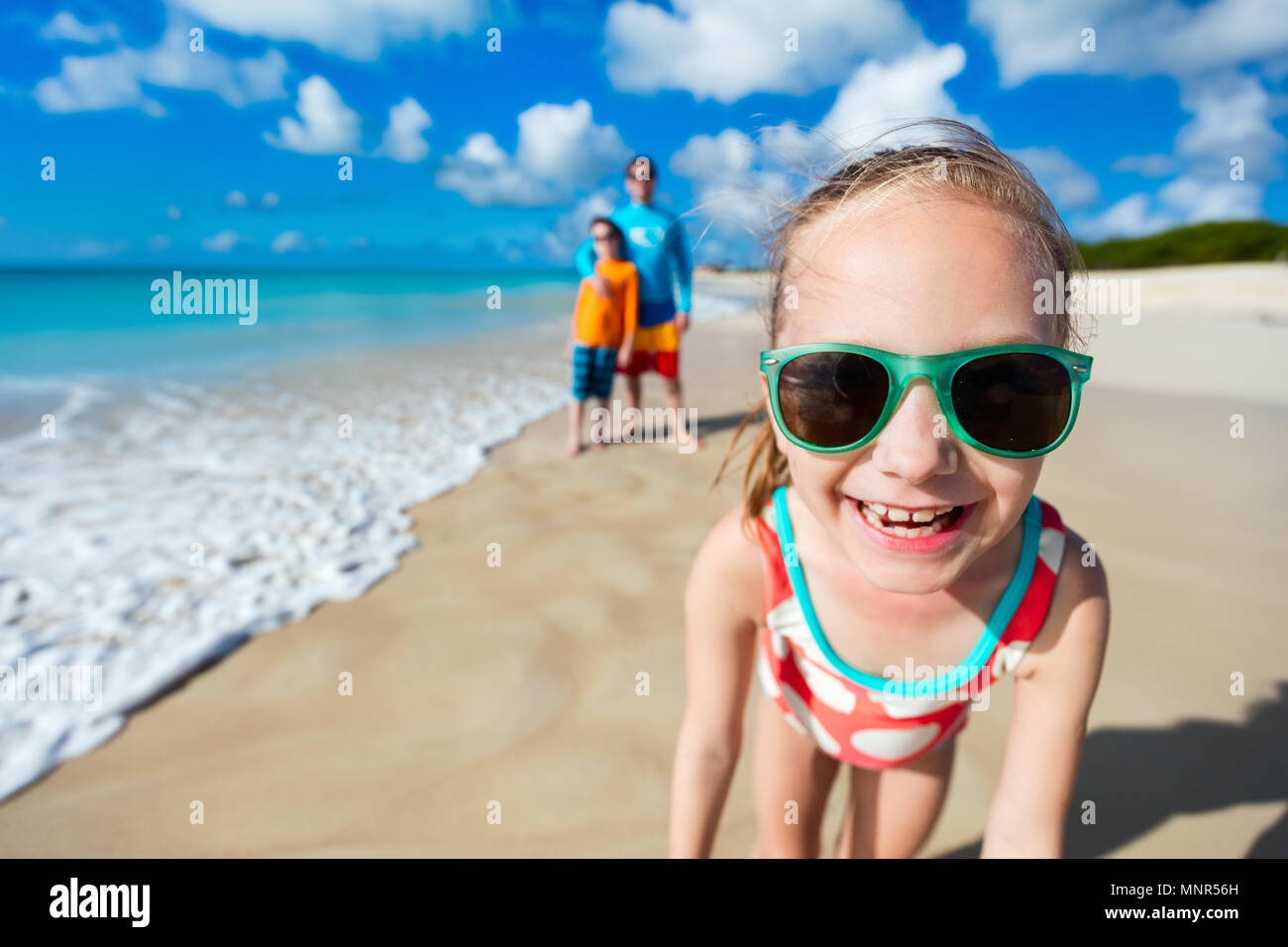Little girl and her family father and brother enjoying beach vacation in Caribbean Stock Photo
