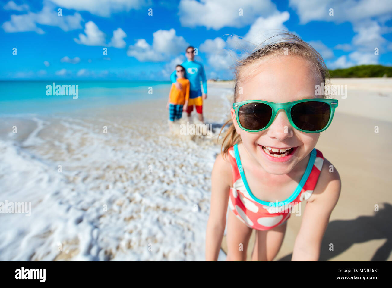 Little girl and her family father and brother enjoying beach vacation in Caribbean - Stock Image