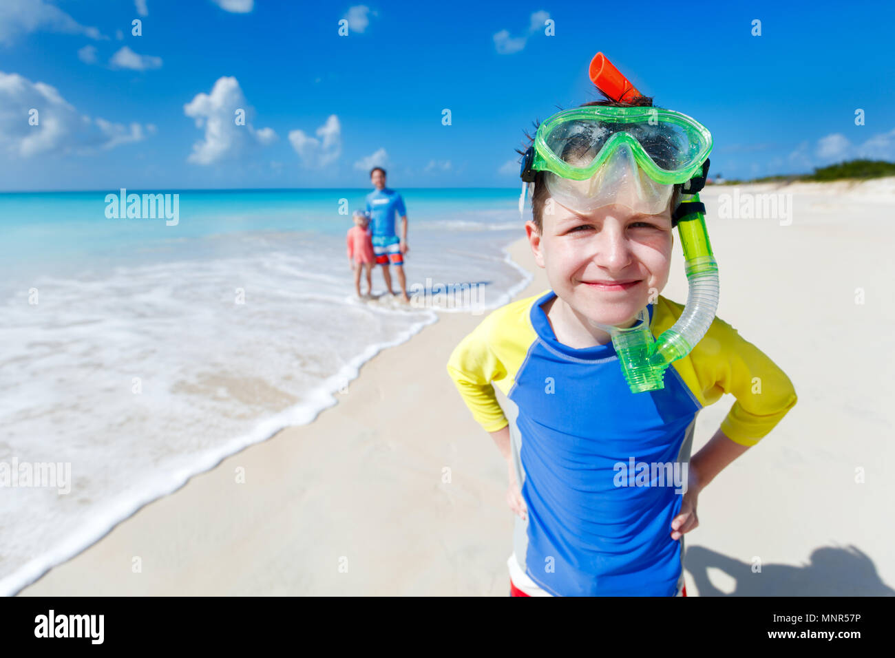 Boy and his family with snorkeling equipment enjoying beach vacation - Stock Image