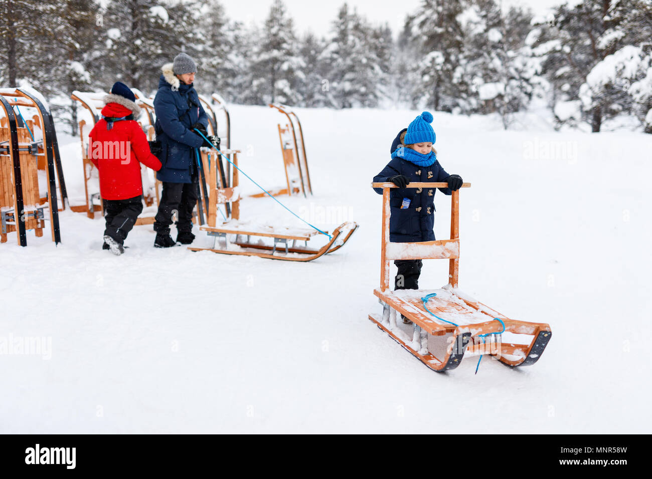 Beautiful family of father and kids enjoying snowy winter day outdoors having fun sledging - Stock Image