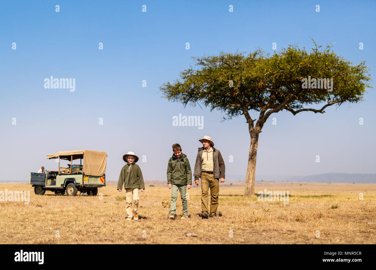 Family of father and kids on African safari vacation enjoying morning game drive Stock Photo