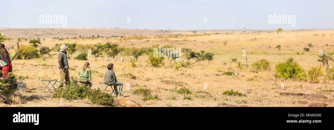 Family of father and kids on African safari vacation enjoying bush breakfast with a view - Stock Image