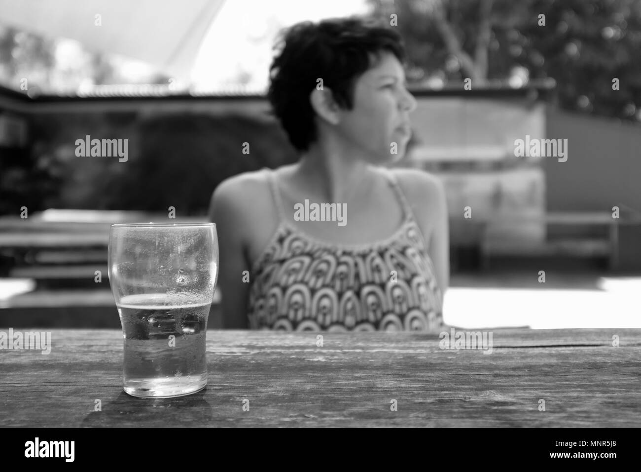 Woman having a glass of beer, Rollingstone Hotel, Bruce Hwy, Rollingstone QLD 4816, Australia - Stock Image
