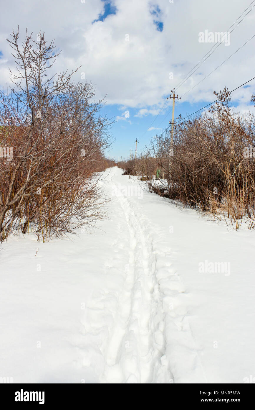 The March footpath on snow suburban array - Stock Image