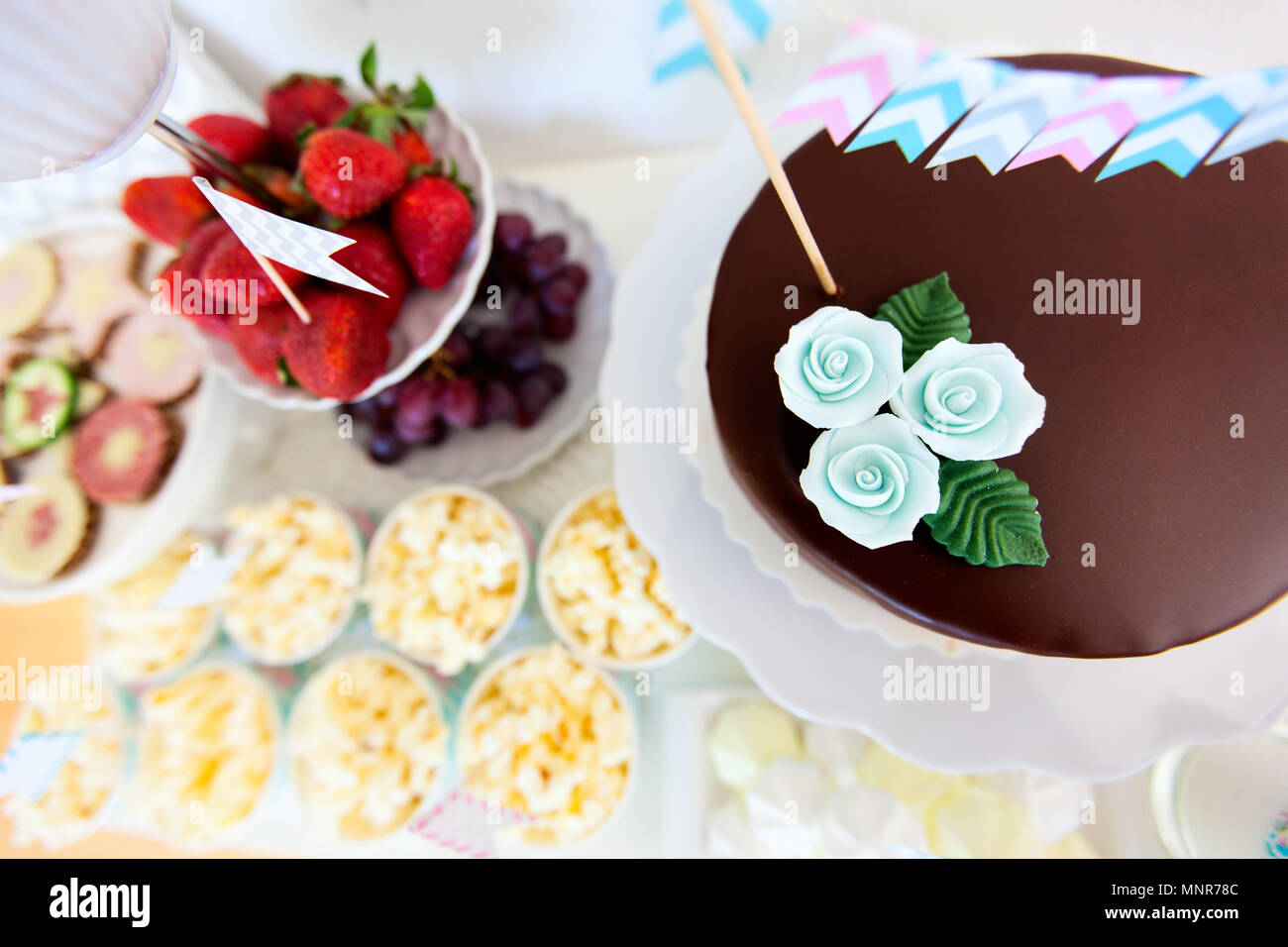 Berries, popcorn, canapes, candies and a chocolate cake on a dessert table at party - Stock Image