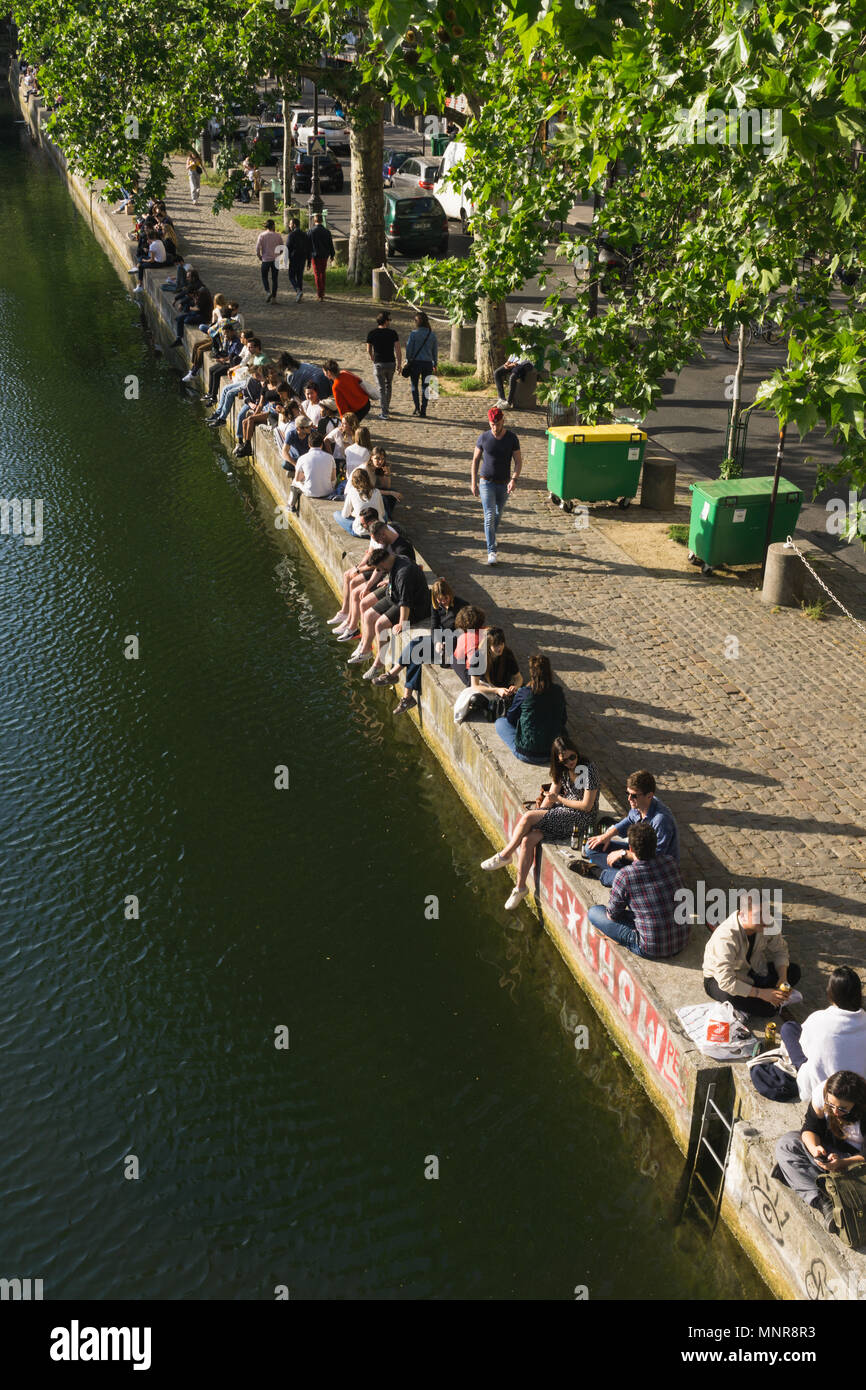 People socialising along the Canal Saint Martin in Paris, France. - Stock Image