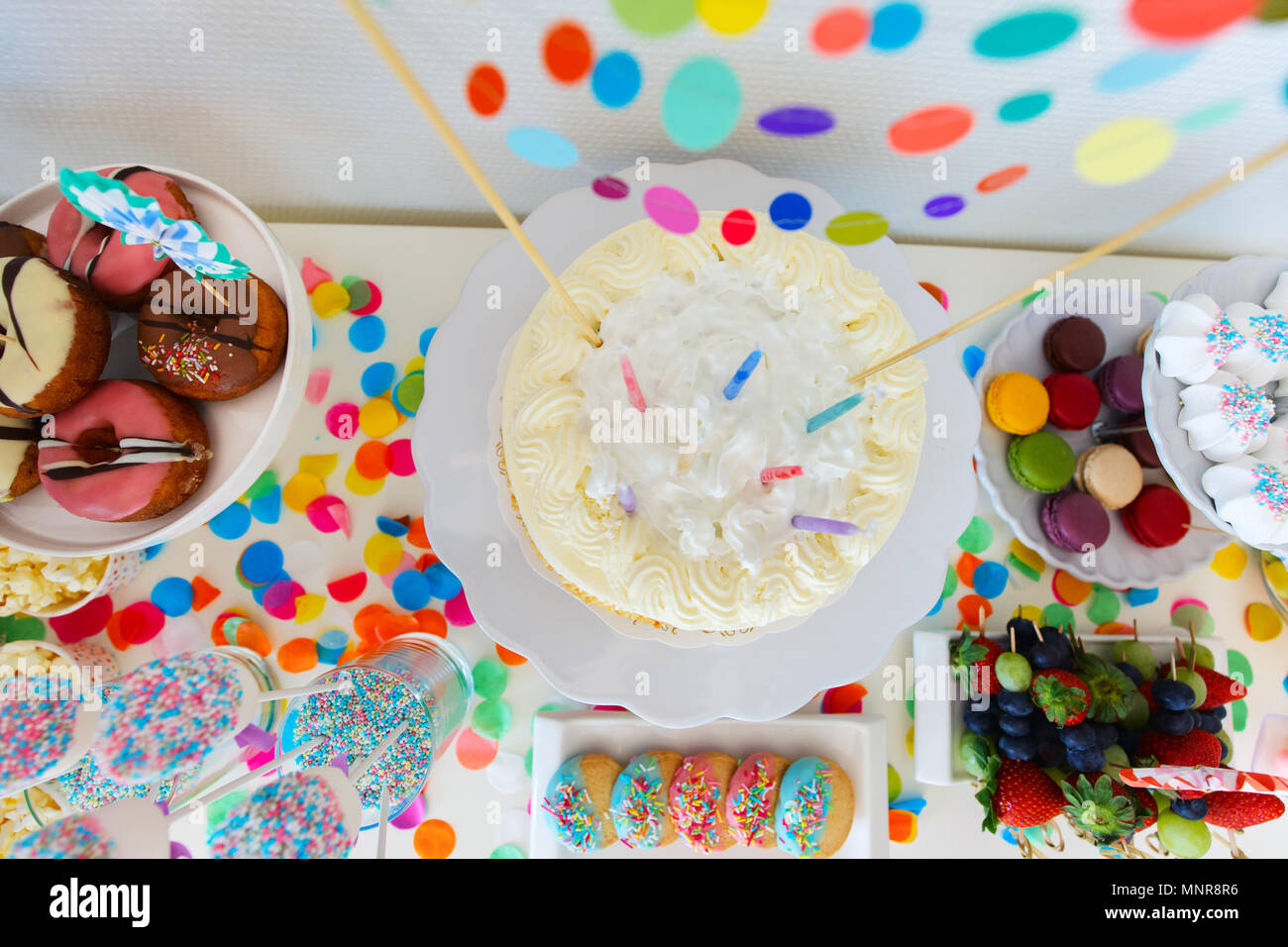 Cake, candies, marshmallows, cakepops, fruits and other sweets on dessert table at kids birthday party - Stock Image