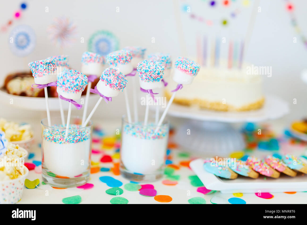 Cake, candies, marshmallows, cakepops, fruits and other sweets on dessert table at kids birthday party Stock Photo