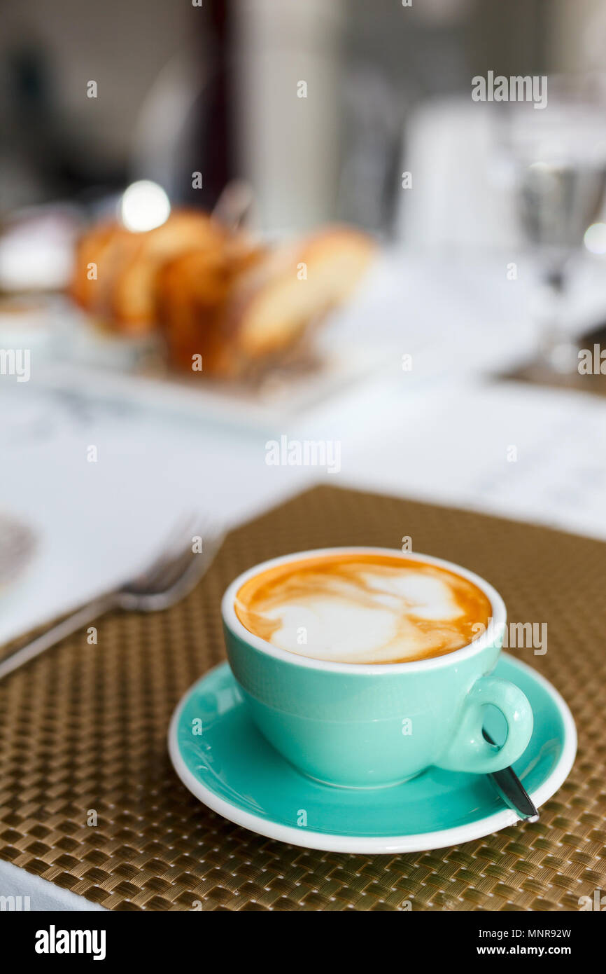Fresh coffee in turquoise cup served for breakfast - Stock Image