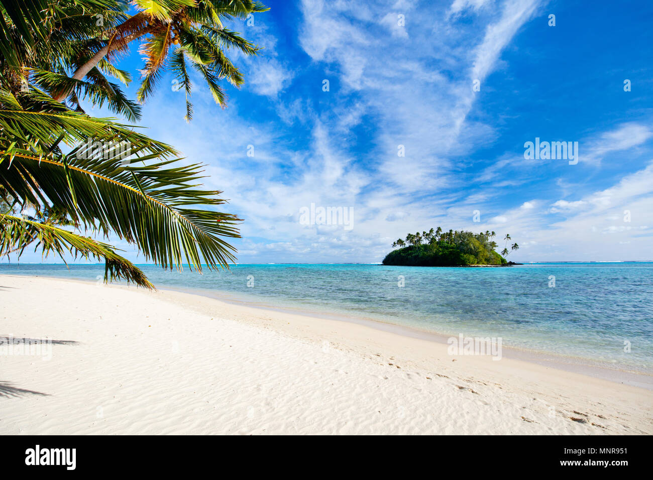 Beautiful tropical beach with palm trees, white sand, turquoise ocean water and blue sky at Cook Islands, South Pacific - Stock Image