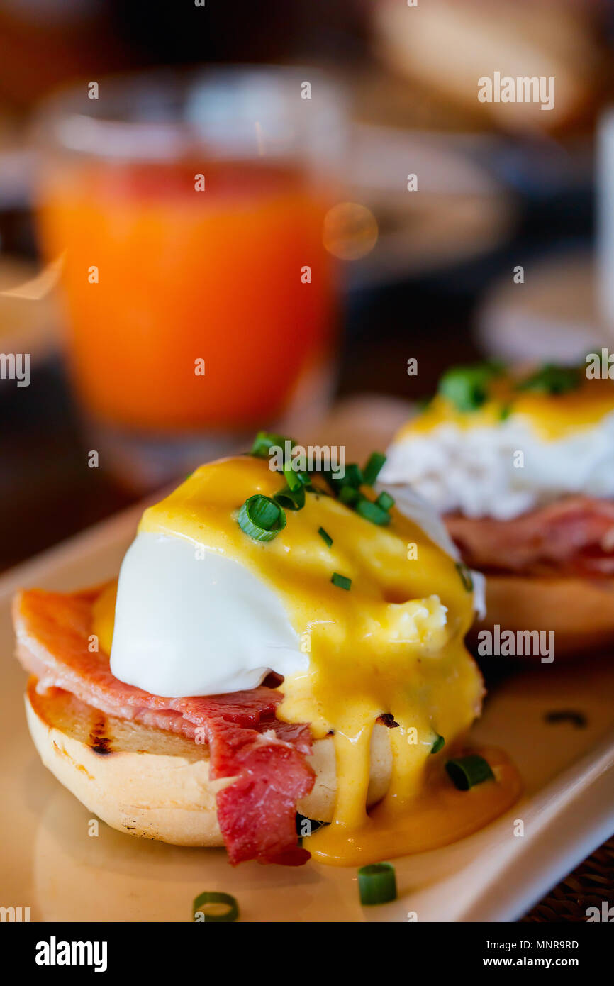 Delicious breakfast with eggs Benedict and juice - Stock Image