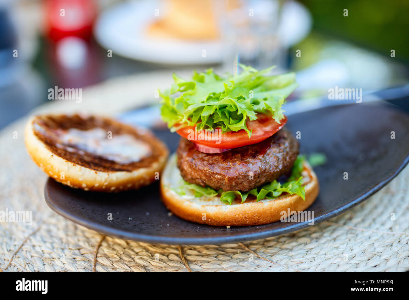 Close up assembling of delicious fresh burger with tomato and fresh green salad - Stock Image