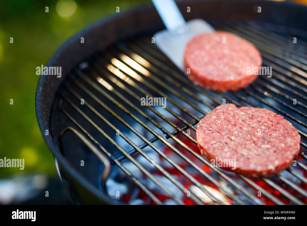 Grilling burger meat cutlets for homemade burger cooking outdoors on summer day - Stock Image