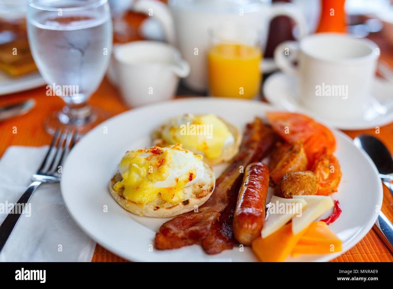 Delicious breakfast with eggs Benedict,  bacon,  orange juice and coffee - Stock Image