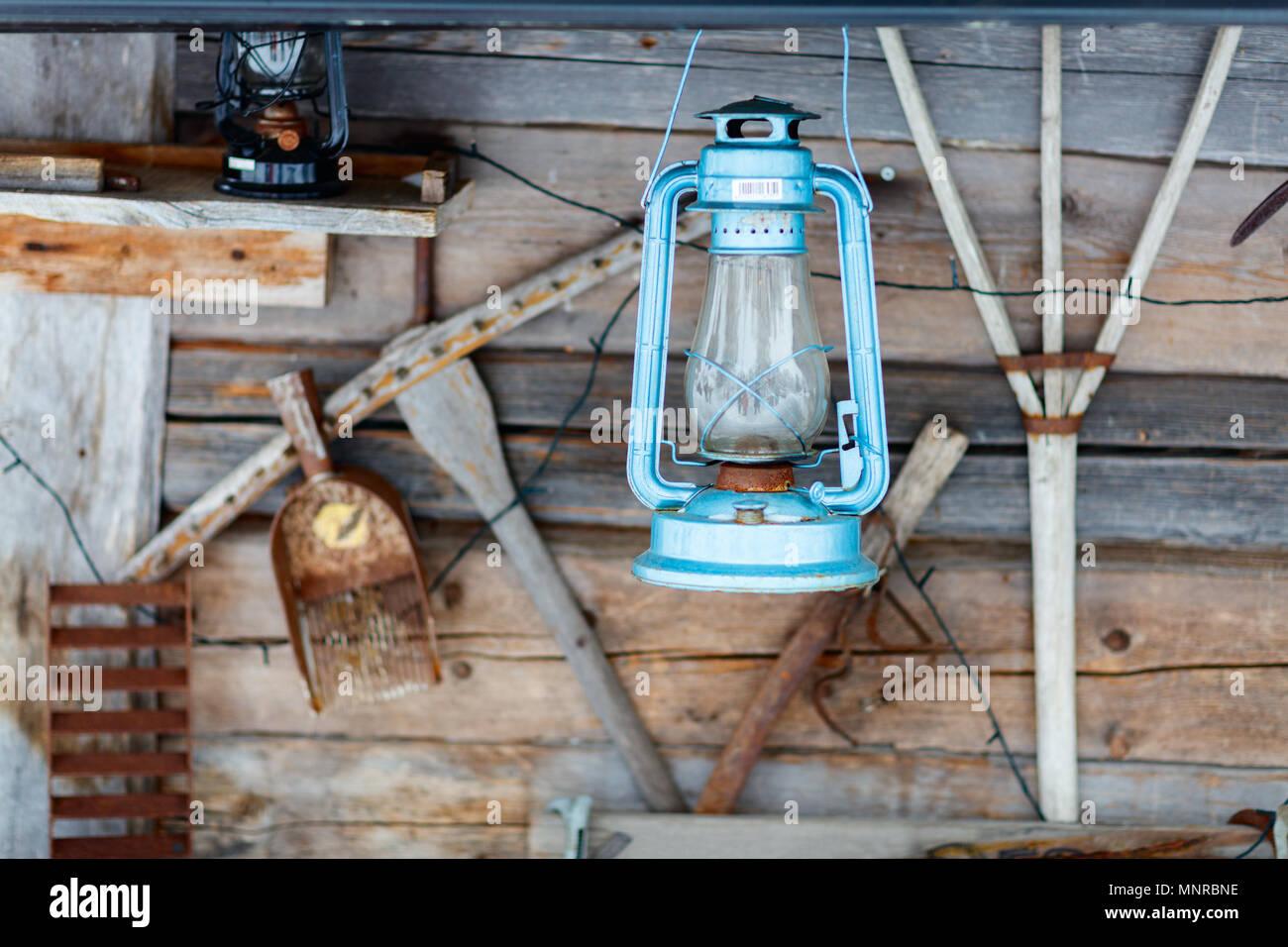 Vintage kerosene oil lantern lamp over wooden background - Stock Image