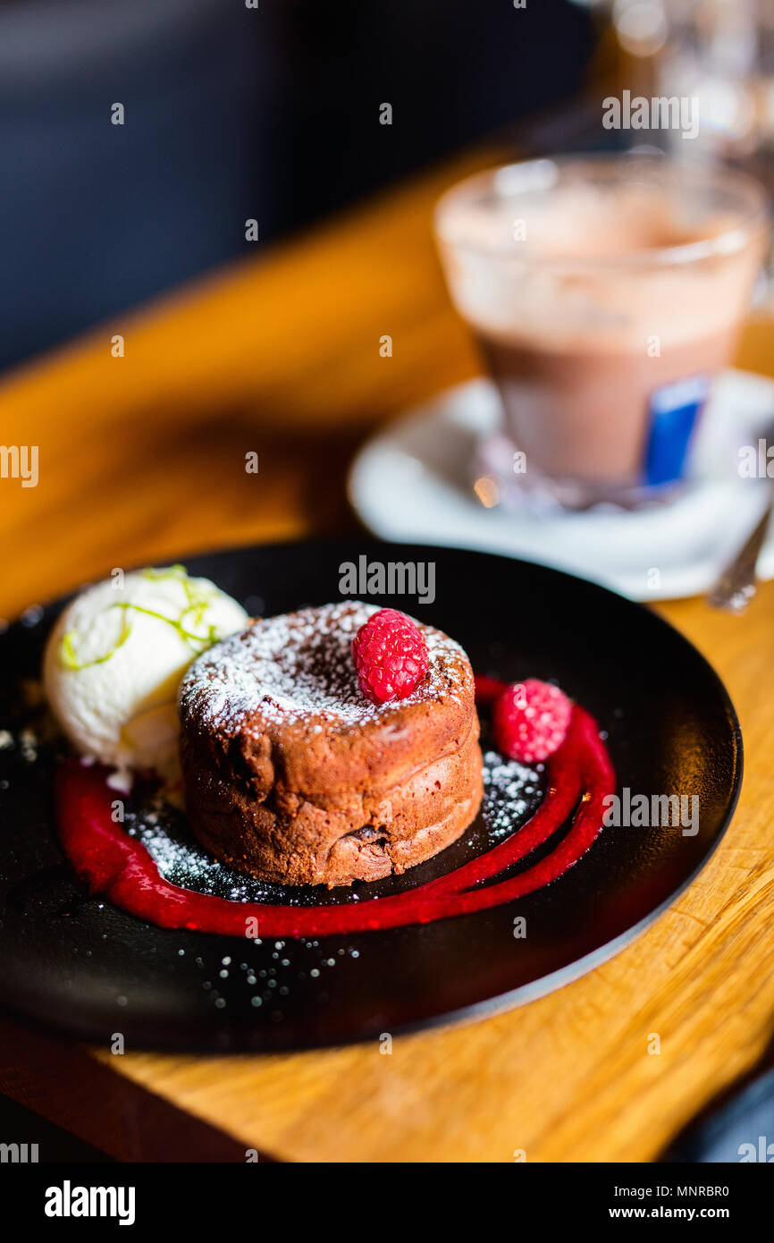 Delicious chocolate fondant dessert served with  vanilla ice cream and fresh berries - Stock Image