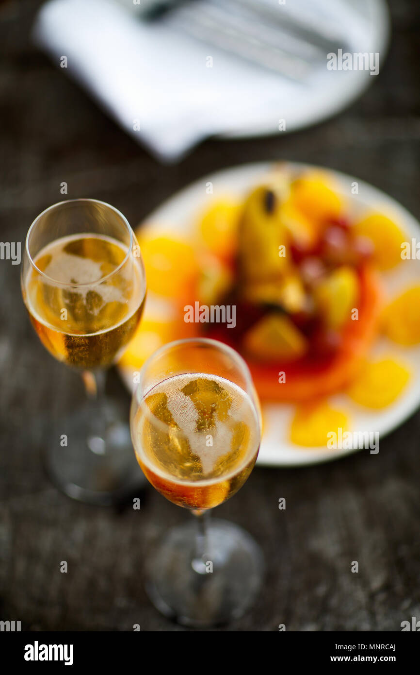 Two glasses with champagne  and fruits on wooden vintage tray served for special occasion or celebration - Stock Image