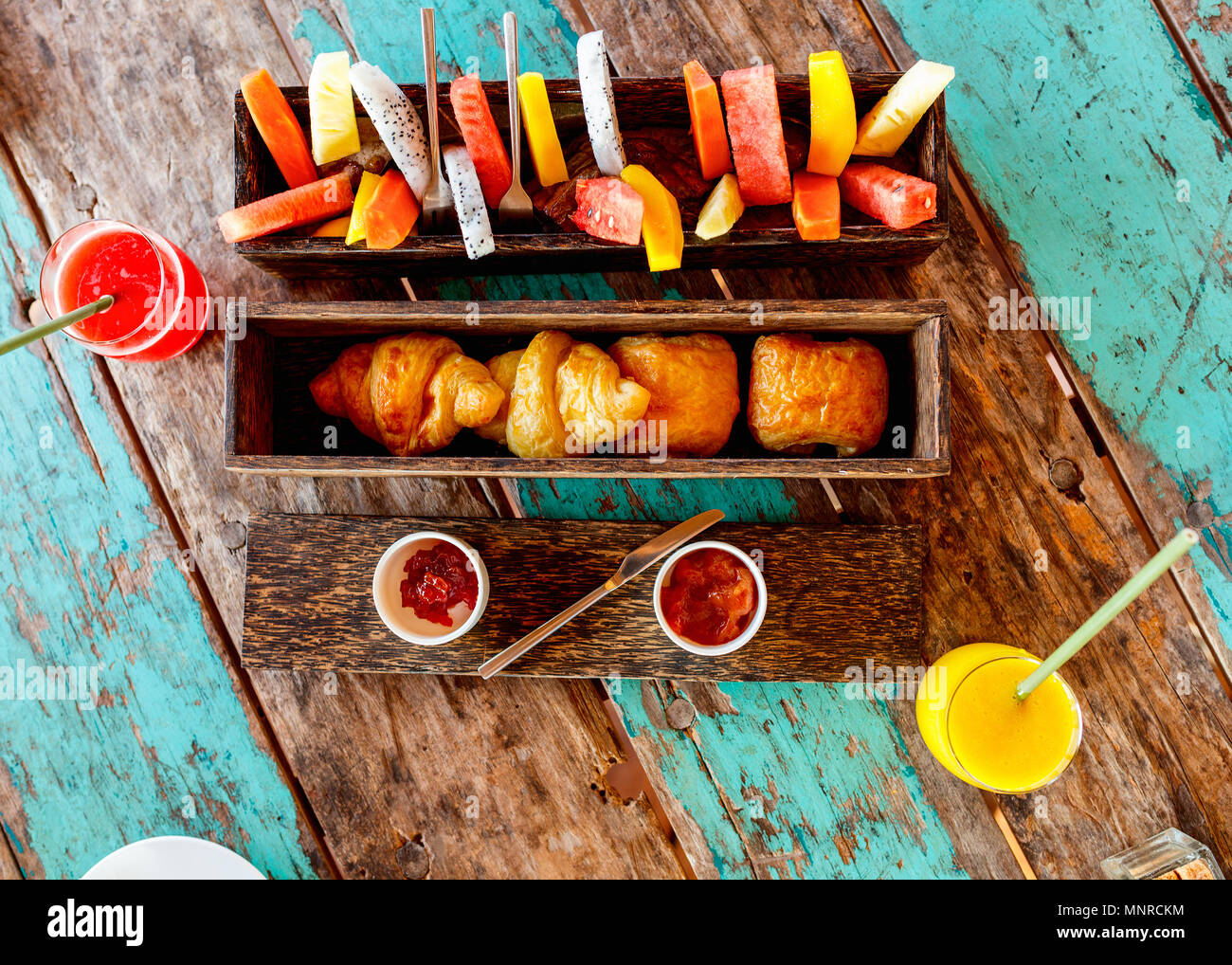 Top view of delicious organic food served for breakfast on rustic wooden table. Fruits,  juice,  croissants and jam flat lay. - Stock Image