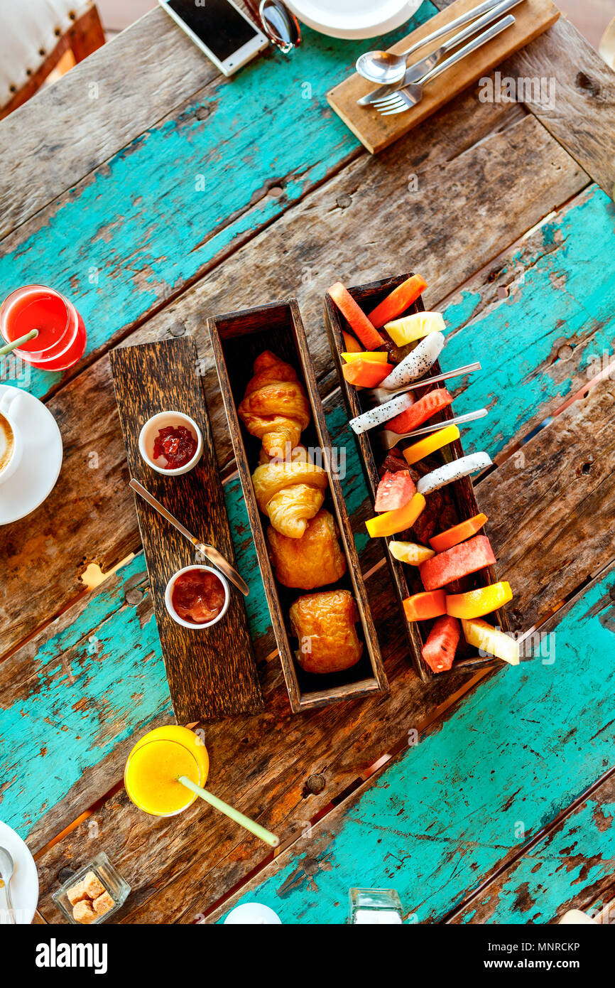 Top view of delicious organic food served for breakfast on rustic wooden table. Coffee,  eggs,  fruits,  juice,  croissants and jam. Stock Photo