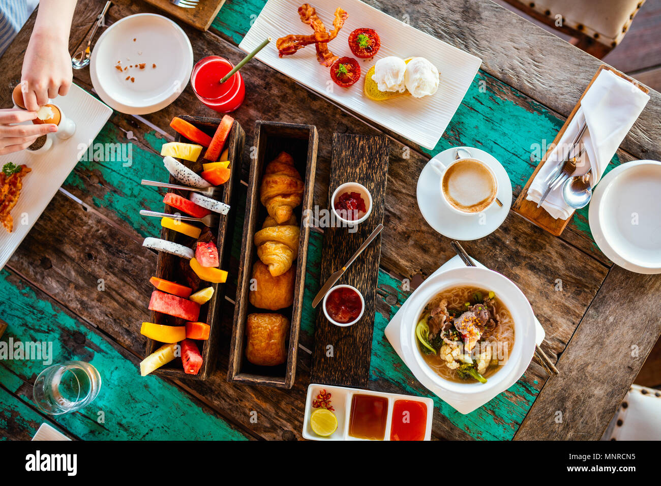 Top view of delicious organic food served for breakfast on rustic wooden table. Coffee,  eggs,  fruits,  juice,  croissants and jam. - Stock Image