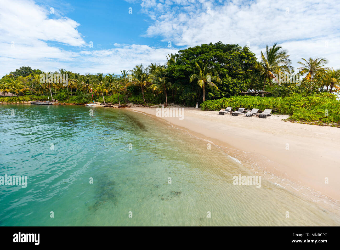 Idyllic tropical island and turquoise ocean water - Stock Image