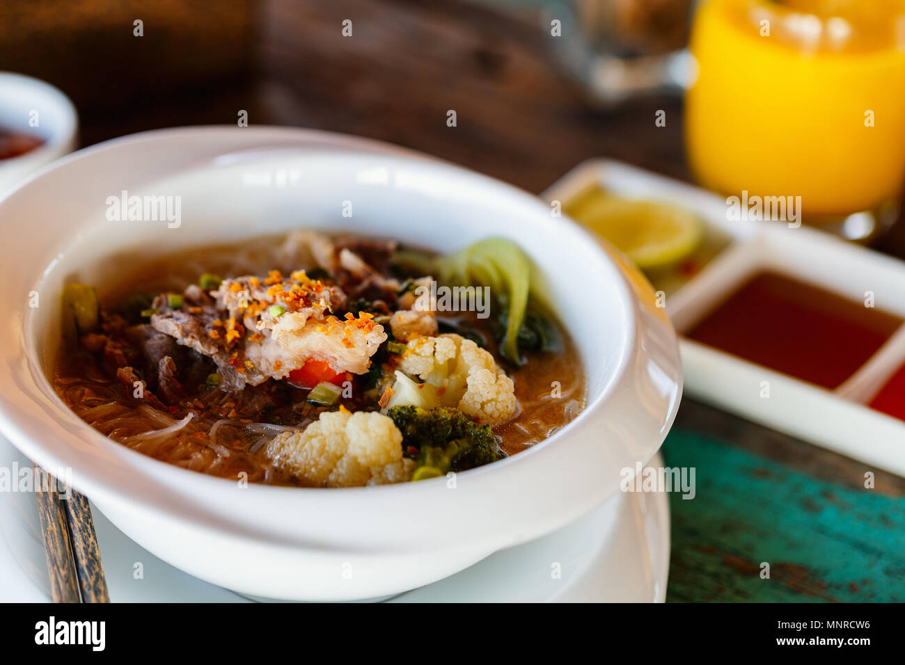 Delicious Asian noodle and meat dish served for breakfast or lunch - Stock Image