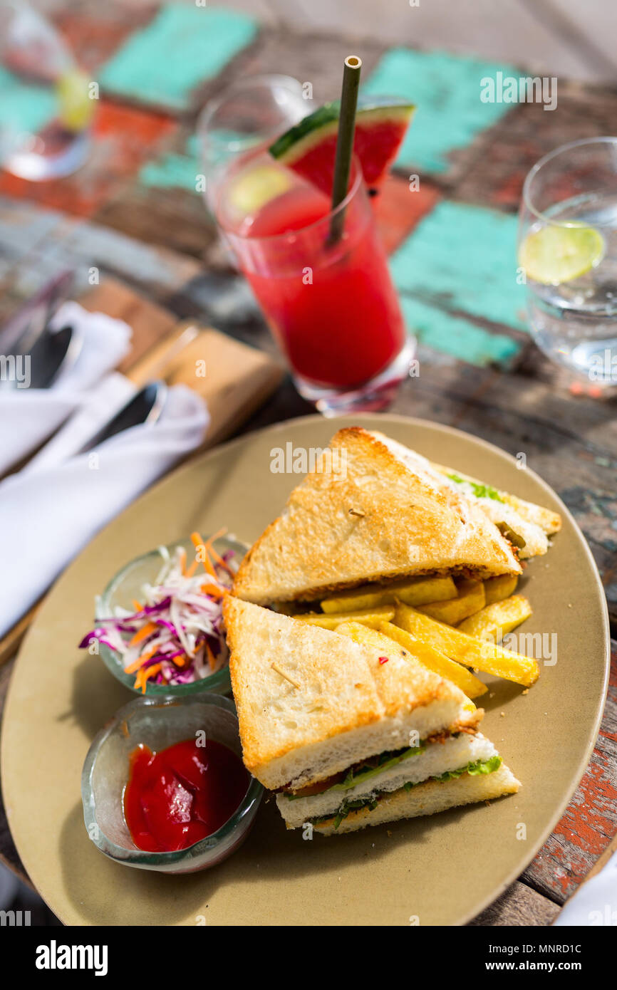 Delicious fresh fish sandwich and green salad served for lunch - Stock Image