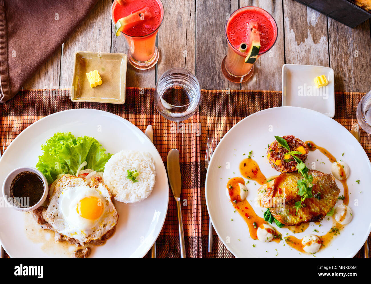 Delicious lunch for two in restaurant of fish,  rice,  fried egg and green vegetables - Stock Image