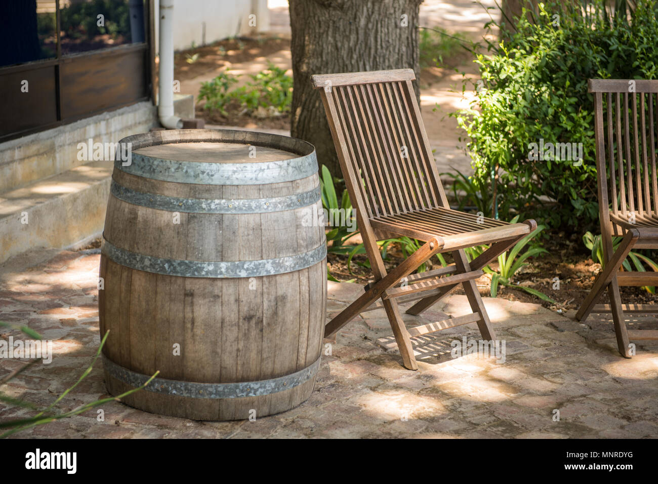 An empty wooden patio chair positioned next to barrel on patio cape town south africa
