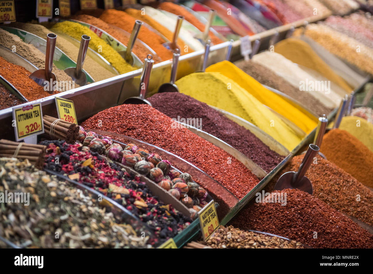 Serve-yourself style bins full of a colorful array of spices and loose teas on display for sale at Istanbul Spice bazaar in Turkey - Stock Image